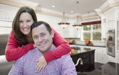 Happy Affectionate Couple In Beautiful New Kitchen. - stock photo