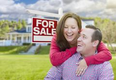 Happy Couple In Front of For Sale Sign and House - stock photo
