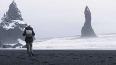 Woman walking along black beach of Iceland. Full HD Video Stock Footage