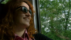 Relaxed young woman on the train smiling near the window seat  Stock Footage