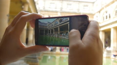 young woman making photos with a smartphone inside a museum, archeological area - stock footage