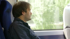 Thoughtful man looking outside the window during a train journey  Stock Footage
