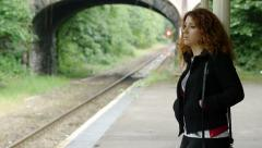 Pensive woman waiting the train on the platform of a little station Stock Footage