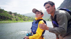 Happy American male parent and son fishing on Colorado River on holiday outdoor - stock footage