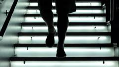 People coming down from a staircase lit: LED lights, glass, modern architecture Stock Footage