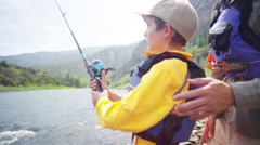 Happy Caucasian boy learning fishing with father on Colorado River on holiday - stock footage