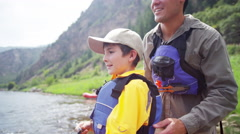 Caucasian dad teaching son fishing on Colorado River on vacation outdoors - stock footage