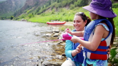 Happy Caucasian daughter learning fishing with mum on Colorado River on vacation - stock footage