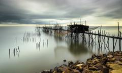 Traditional bamboo fisherman jetty during windy and moving clouds sunset. - stock photo