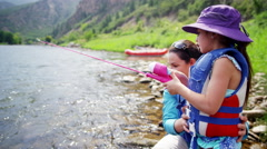 Happy mother and daughter using rod and reel casting line on Colorado River - stock footage