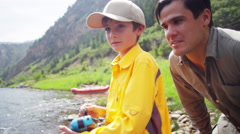American dad and son using rod and reel casting line on Colorado River - stock footage