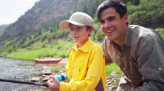 Confident father and son using rod and reel casting line on Colorado River - stock footage