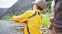 Caucasian American male parent and son fishing on Colorado River outdoors - stock footage
