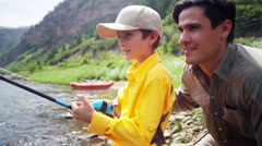 Portrait of Caucasian dad and son fishing on Colorado River on holiday outdoors - stock footage