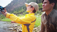 Happy father and son using rod and reel casting line on Colorado River - stock footage