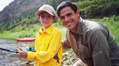 Portrait of Caucasian male parent and son fishing on Colorado River outdoor - stock footage