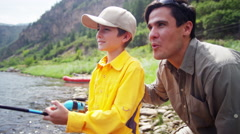 Happy American Caucasian dad and son enjoying fishing on Colorado River outdoors - stock footage