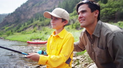 Portrait of Caucasian male parent and boy enjoying fishing on Colorado River - stock footage