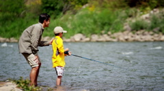 American Caucasian dad and son using rod and reel casting line on Colorado River Stock Footage
