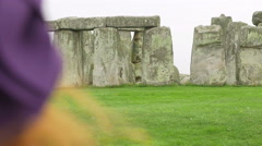 young woman with smartphone making photos to stonehenge - stock footage