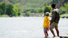 Happy American son learning fishing with father on Colorado River on vacation - stock footage