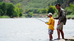 Caucasian father teaching son fishing on Colorado River on holiday outdoors - stock footage