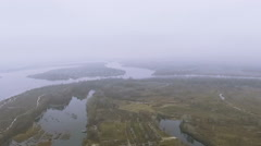 Flight over  field, lake, river in foggy  cloudy day with  turn. Aerial - stock footage