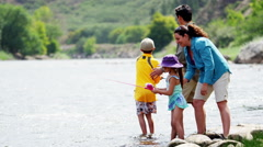 Happy Caucasian parent and children enjoying fishing on Colorado River outdoors - stock footage