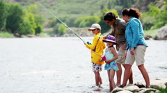 Happy Caucasian family having fun together fishing on Summer holiday outdoors - stock footage