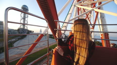 Tourism: pretty woman sightseeing city from height in the cabin of ferris wheel Stock Footage