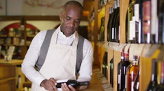 4K Portrait of friendly shopkeeper standing by shelves in wine shop Stock Footage