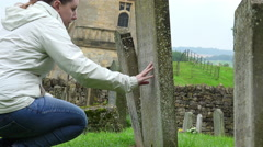 praying on the tomb of the father: cemetery, religion, searching of god, faith  - stock footage