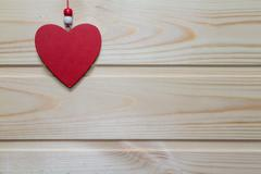 Wooden red heart suspended on a natural wood background.Valentine day. Stock Photos
