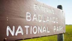 Badlands sign for South Dakota, National Park desert buttes USA - stock footage