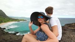 Young active couple sitting and looking at view in Makapuu Lookout, Oahu, Hawaii - stock footage