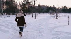 Dog runs with the girl. Winter. Slowing down. Stock Footage