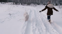 Cheerful girl runs with a white dog. Winter. Slow motin Stock Footage