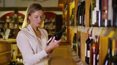 4K Portrait of friendly shopkeeper standing by shelves in wine shop - stock footage