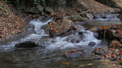 Mountain stream flowing and making cascades, slow motion, big stones in water. Stock Footage