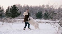 Cheerful girl playing with a dog on a snowy meadow. Slowing down. Stock Footage