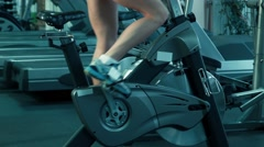 Athletic female pedaling on the simulator on a stationary bike at the gym. Stock Footage