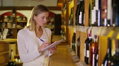 4K Portrait of friendly shopkeeper checking stock in wine shop - stock footage