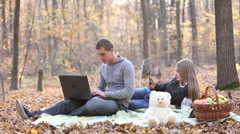 couple with laptop in the autumn forest - stock footage