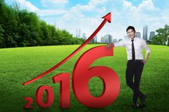 Asian business person lean next to 2016 number - stock photo