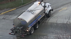 Street cleaning water truck hosing down roads in the city Stock Footage