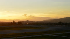 Airplane landing in airport at sunset - stock footage