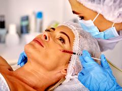 Woman middle-aged in spa salon with beautician. Female giving botox injections - stock photo