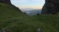 Aerial view of couple walking by Old Man of Storr Scotland - stock footage