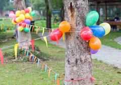 outdoor party in garden decorated with colorful ballons and flags - stock photo