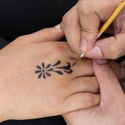 body paint, artist used paintbrush drawing art on hand person - stock photo